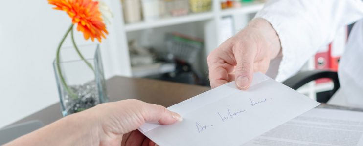 Doctor handing referral to patient in medical office
